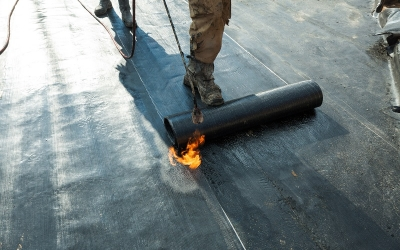 Installation of roll roofing waterproofing propane blowtorch during construction