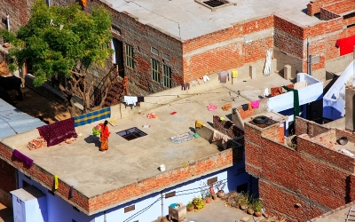 Local woman walking on a flat roof of the house in Jaipur, Rajas